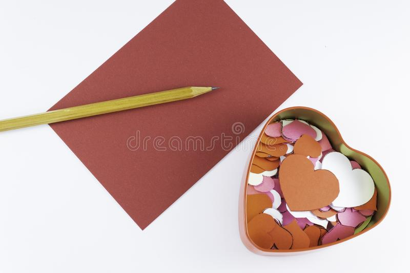 Wooden pencil on an empty red letter near to a box for valentines and different colors inside on a white background Valentine`s. Day or festive concept Letter royalty free stock image