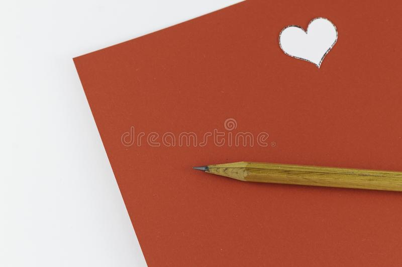 Wooden pencil on empty red letter with small white heart on white background Valentine`s day. Or festive concept Letter or invitation inside Minimalist concept stock image