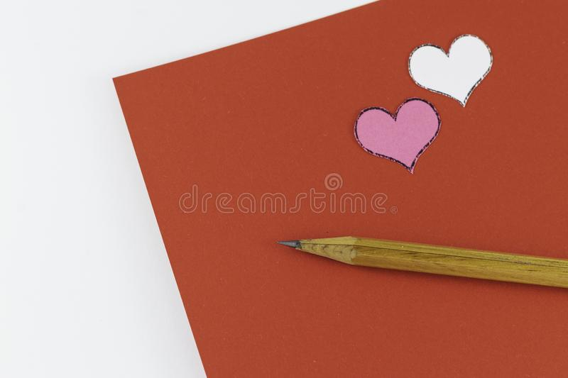 Wooden pencil on empty red letter with small white and pink hearts on white background Valentine`s day. Or festive concept Letter or invitation inside royalty free stock images
