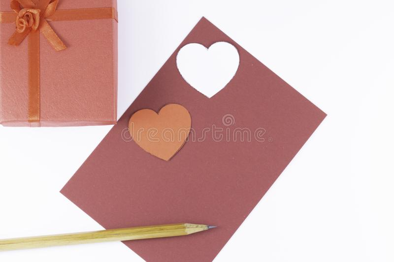 Wooden pencil on an empty red letter and two white and red hearts with gift box near on a white background Valentine`s day. Or festive concept Letter or stock image