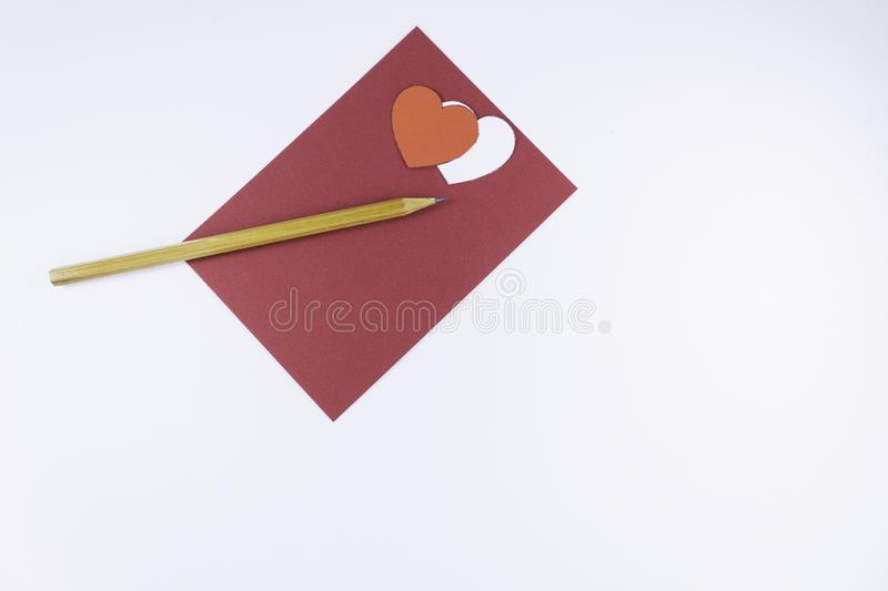 Wooden pencil on an empty red letter and two white and red hearts near on a white background Valentine`s day. Or festive concept Letter or invitation inside stock photography