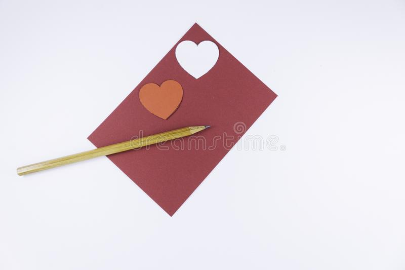 Wooden pencil on an empty red letter and two white and red hearts near on a white background Valentine`s day. Or festive concept Letter or invitation inside royalty free stock photography