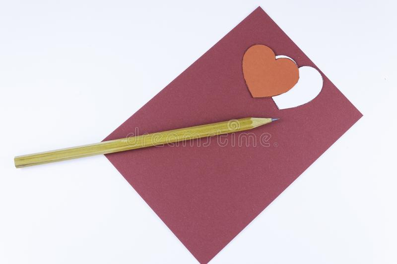 Wooden pencil on an empty red letter and two white and red hearts near on a white background Valentine`s day. Or festive concept Letter or invitation inside royalty free stock images