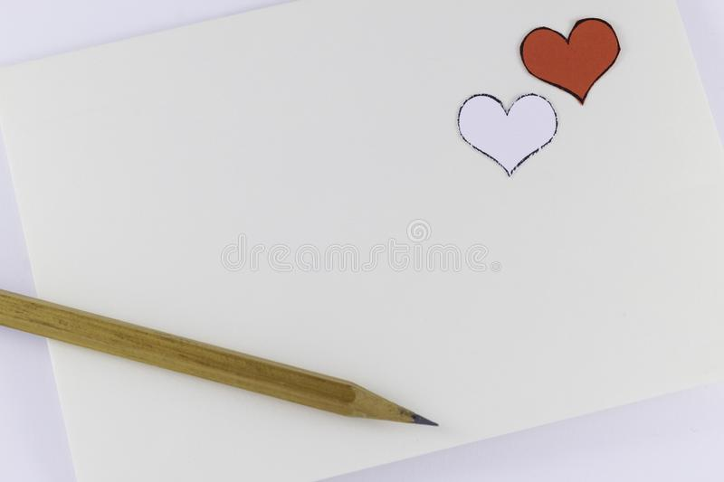 Wooden pencil on empty white letter with small white and red hearts on white background Valentine`s day. Or festive concept Letter or invitation inside stock photography