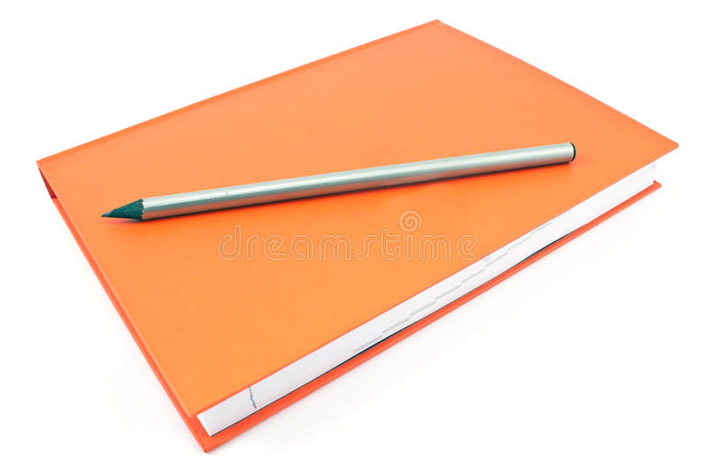 Wooden pencil on red notebook. Isolated on white stock images