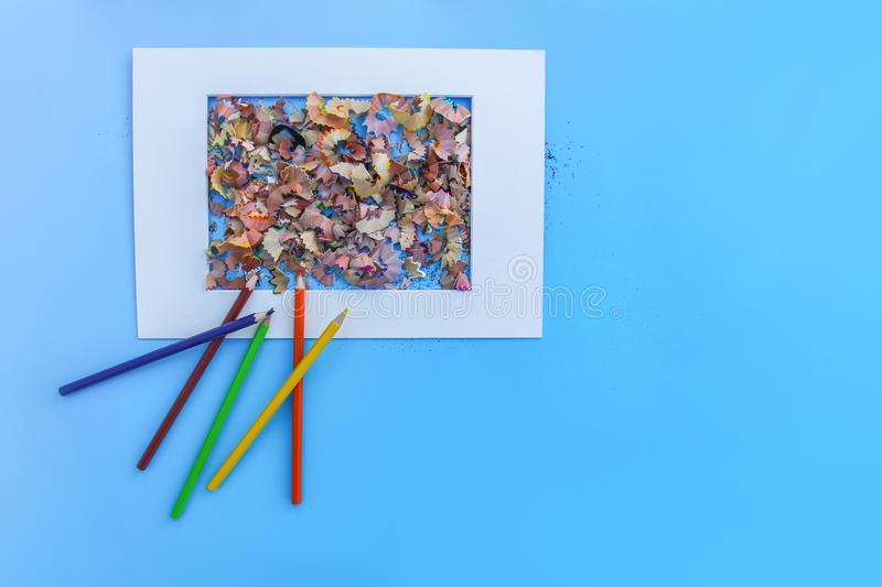 Wooden pencil shavings from sharpener and colored pencils on blue background with white frame. royalty free stock photos