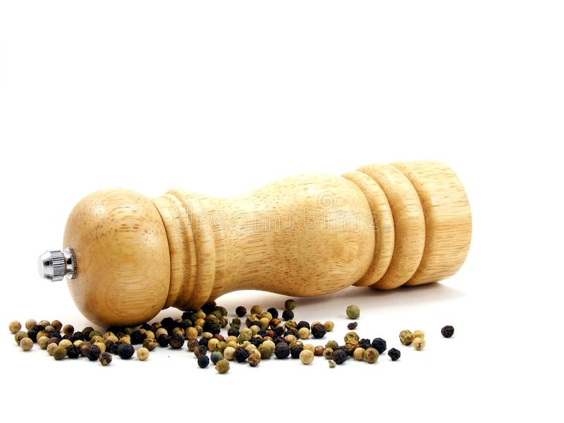 A wooden peppermill with peppercorns