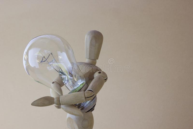 Wooden person holds electric bulb in hand stock photos