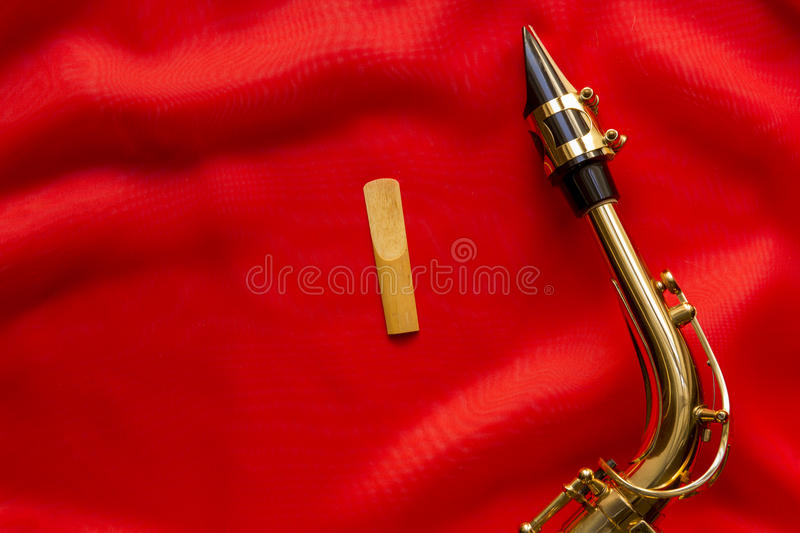 Wooden petal and saxophone. Mouthpiece on a red background stock photography