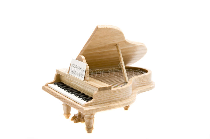 Wooden piano. Side view of small wooden piano isolated on a white background stock images