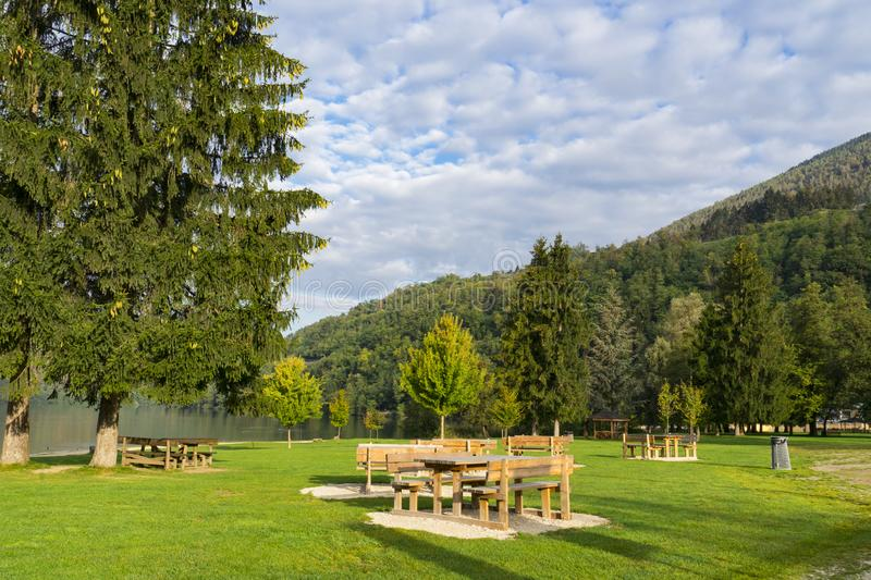 Wooden picnic tables on grass field, along Lake Levico Terme, Italy. Recreation field with empty wooden picnic tables in spa town Levico Terme, Italy, Europe stock photography