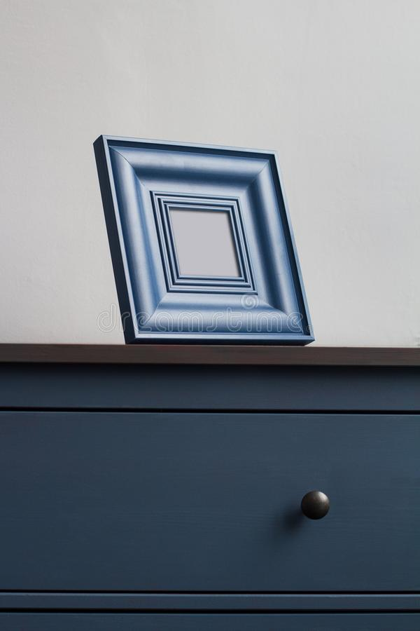 Wooden picture frame on blue chest of drawers royalty free stock photos