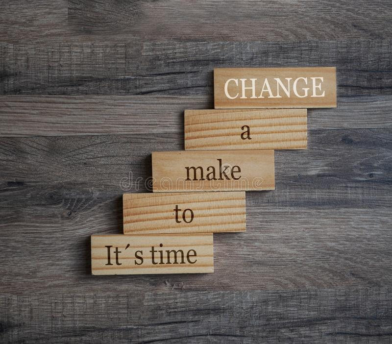 Wooden pieces on a wooden background showing the words Its time to make a change. Wooden pieces showing the words Its time to make a change royalty free stock photography