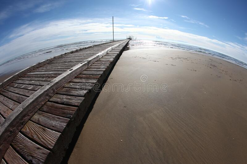 Wooden pier on beach royalty free stock photo