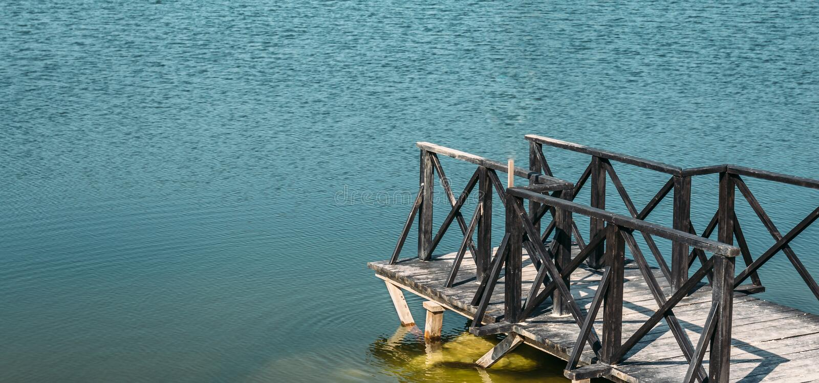 Wooden pier with blue sea or lake, panoramic photo with copy space stock photo