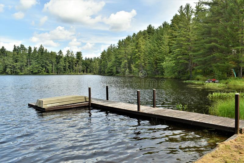 Wooden Pier and boat on Leonard Pond, Colton,  St. Lawrence County, New York, United States. NY. US. USA. Wooden dock and boat located on  Leonard Pond, located stock photos