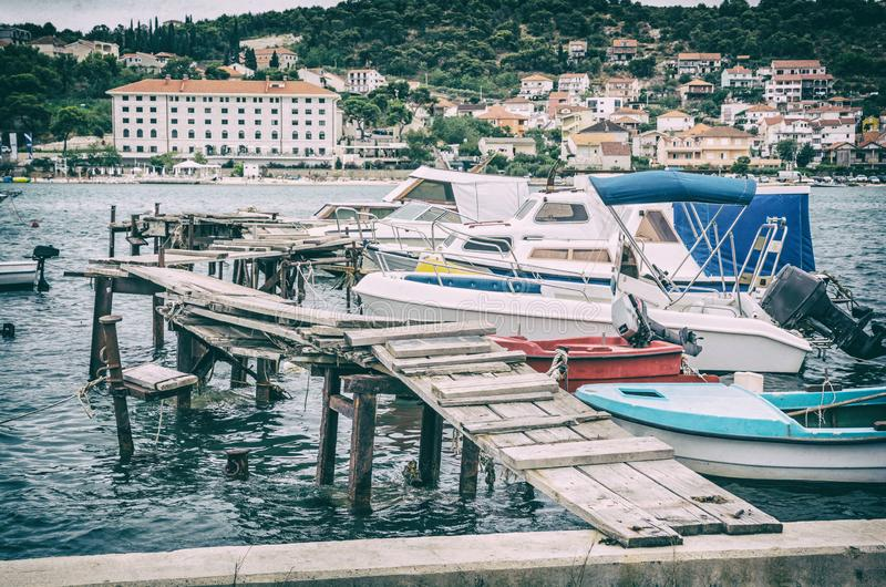 Wooden pier with boats in harbor, Trogir, analog filter. Wooden pier with boats in harbor, Trogir, Croatia. Travel destination. Sunset scene. Analog photo filter royalty free stock images