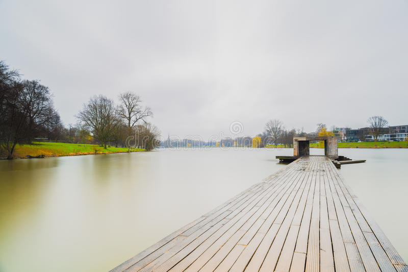 Wooden pier and boats in Muenster Aasee while raining... royalty free stock images