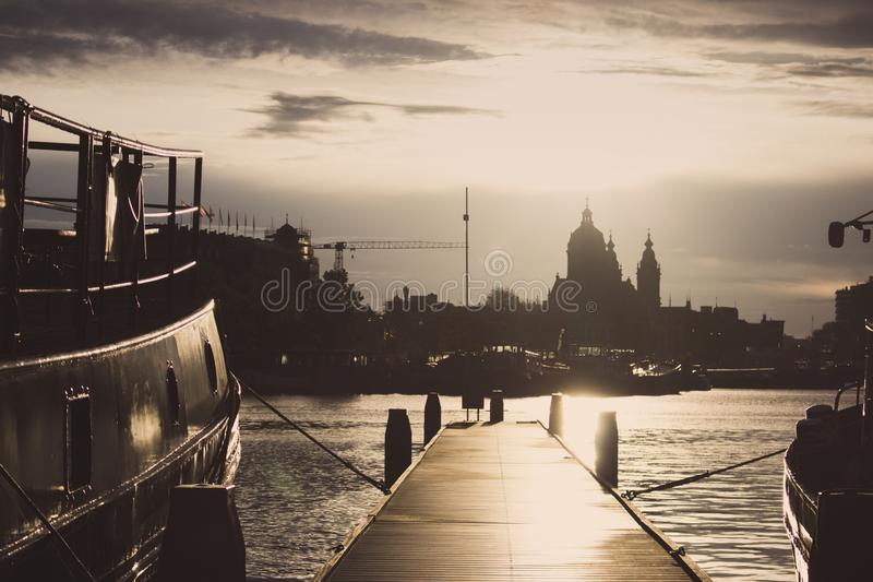 Wooden pier with boats at sunset in Amsterdam dock. Amsterdam city silhouettes in evening dusk light. stock images