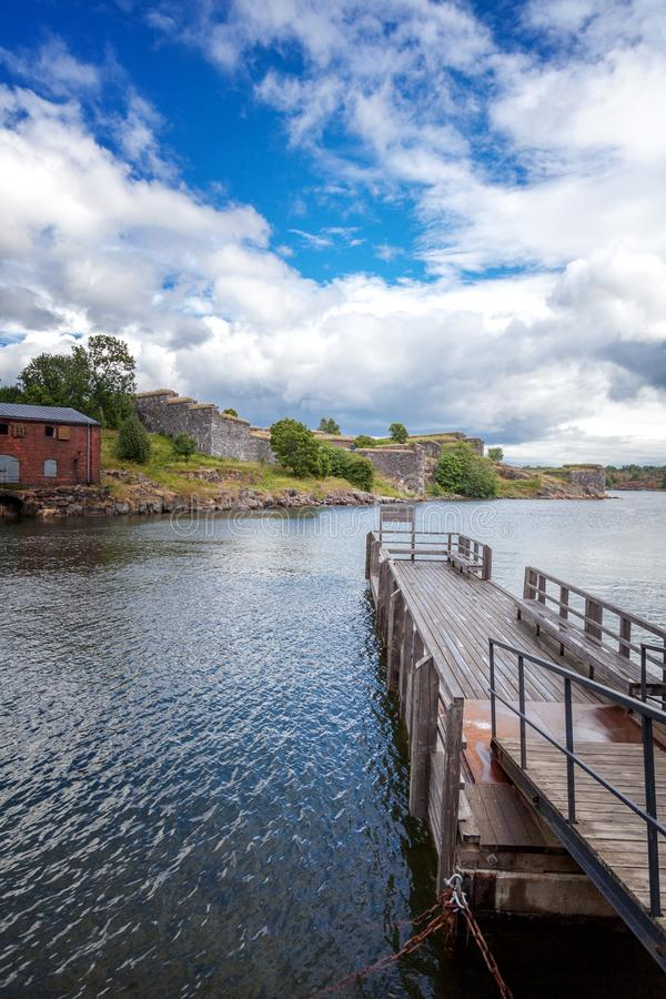 The wooden pier for boats and yachts on the island of Suomenlinna, fortress view, beautiful bright landscape. Travel to Northern stock photography
