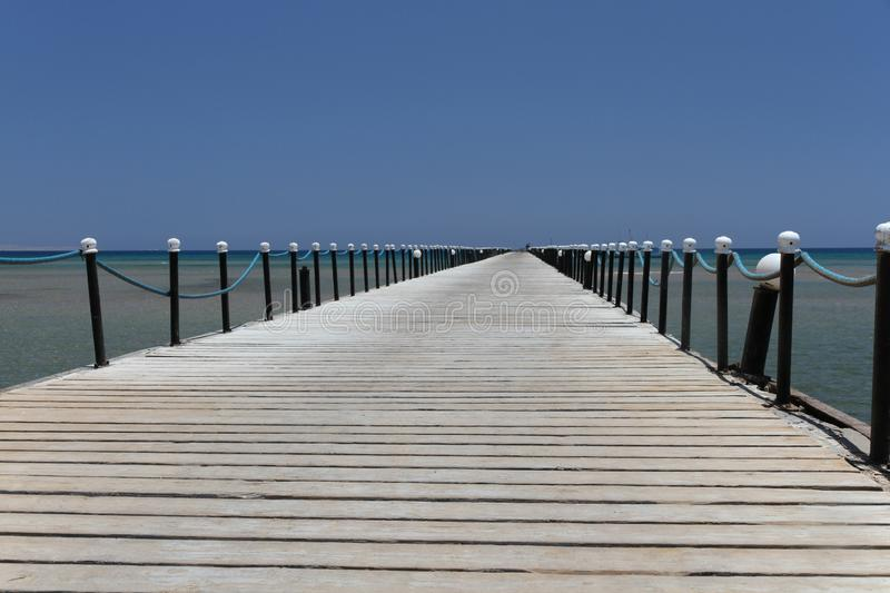 Wooden pier on coast of Coral beach of Red Sea in Hurghada royalty free stock image