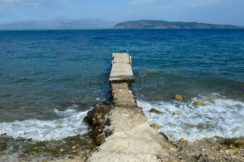 Wooden pier connected by a concrete passage on the bottom there are islands in the sea there is none stock image