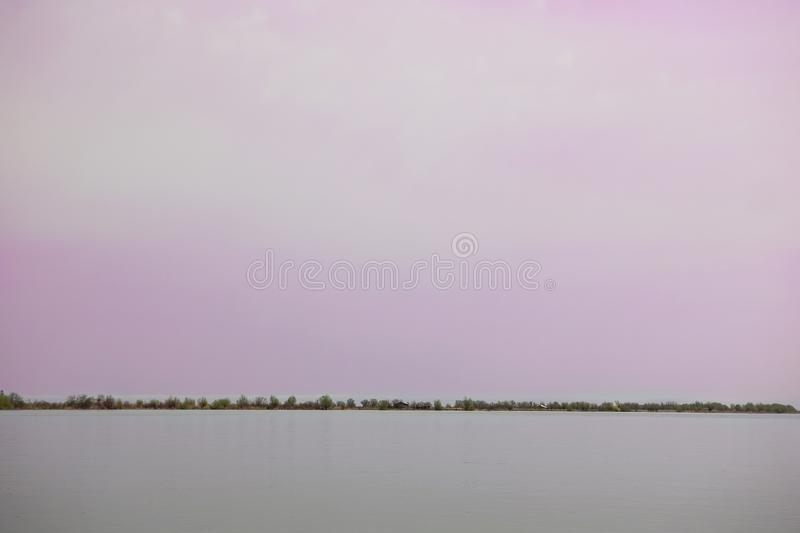 Wooden pier on the Danube River. Spring on Danube river. Flooded trees in the green meadow over the banks of the Danube river in early spring. Danube natural stock photo