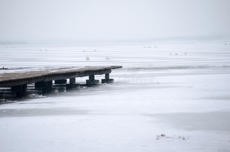 Wooden pier on frozen lake on foggy winter morning. stock images