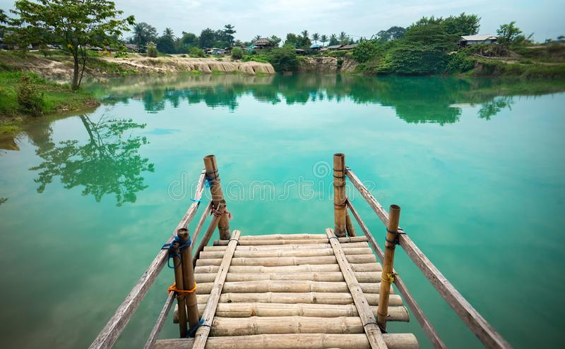 Wooden Pier on Green Blue Lagoon, Tropical Paradise. Traditional Bamboo Pier or Jetty on Lakeside. Concept of New Beginning of Exp stock photo