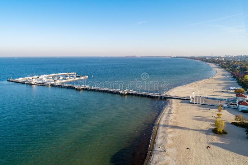 Wooden pier and beach in Sopot Poland. Aerial view. Wooden pier with harbor, marina with yachts and beach in Sopot resort near Gdansk in Poland in sunset light royalty free stock photo