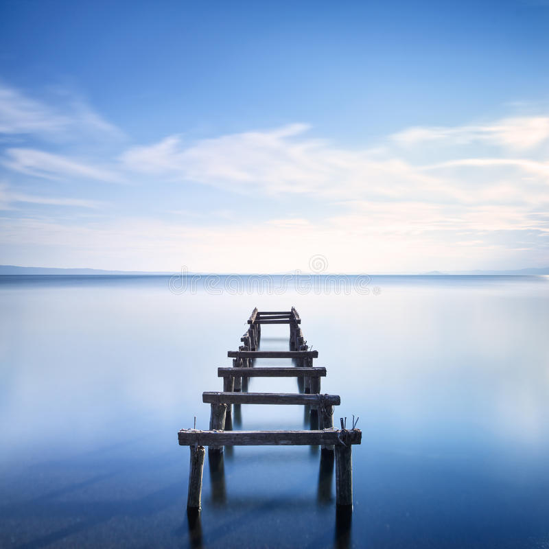 Wooden pier or jetty remains on a blue lake. Long Exposure. stock photography