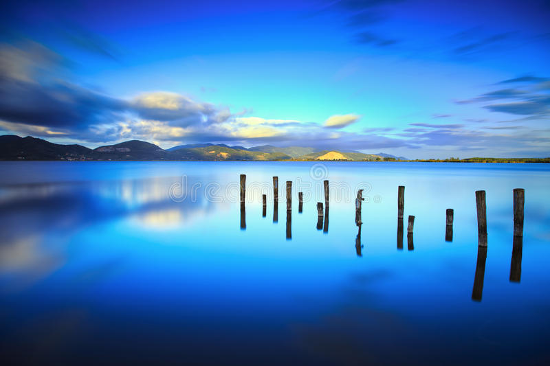 Wooden pier or jetty remains on a blue lake sunset and sky reflection on water. Versilia Tuscany, Italy. Wooden pier or jetty remains on blue lake sunset and sky stock images