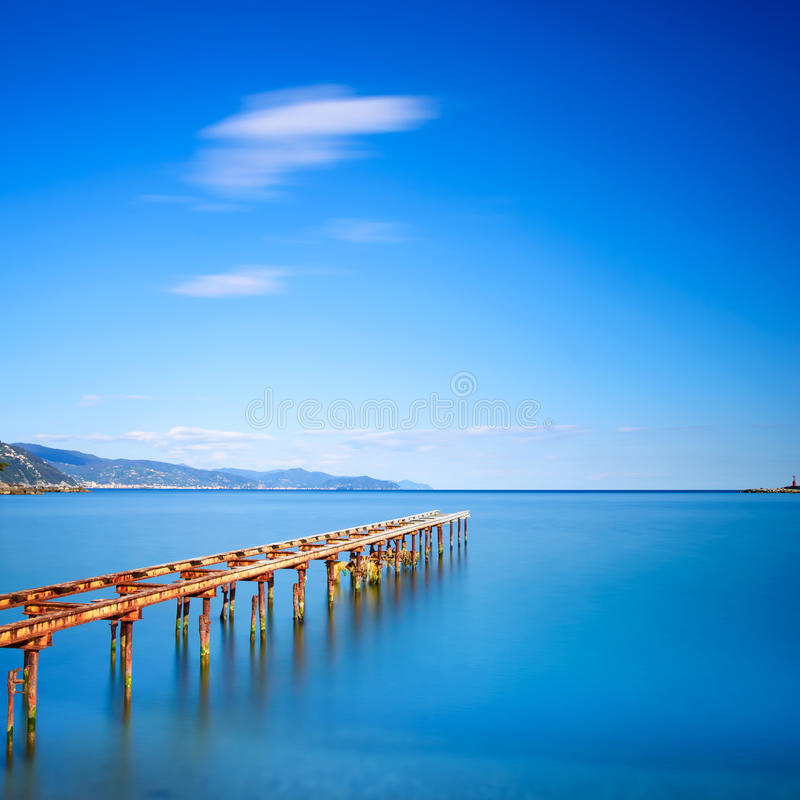 Wooden pier or jetty remains on a blue ocean lake. Long Exposure. Wooden pier or jetty remains on a blue ocean sunset. Ligury, Italy. Long Exposure photography royalty free stock photos