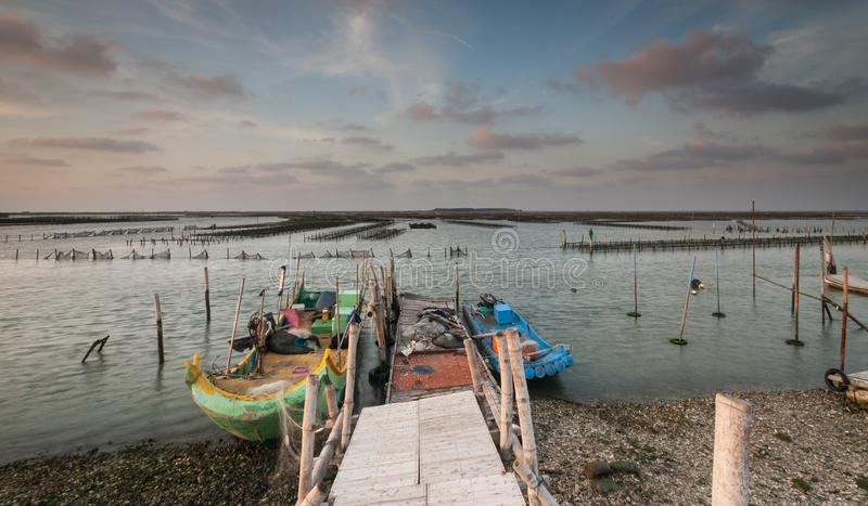 Wooden pier by a lake with two boats next to it with the beautiful cloudy sky in the background royalty free stock photo