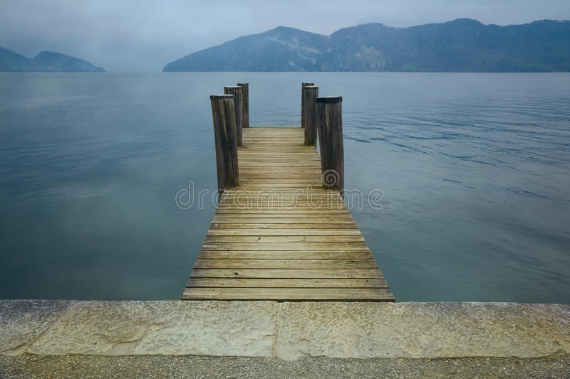 Wooden pier on lake. Vacation, tourism and adventure concept. Retro filter. Effect royalty free stock images