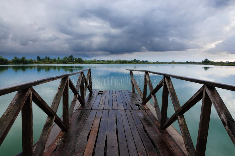Wooden pier leading to the lake royalty free stock images