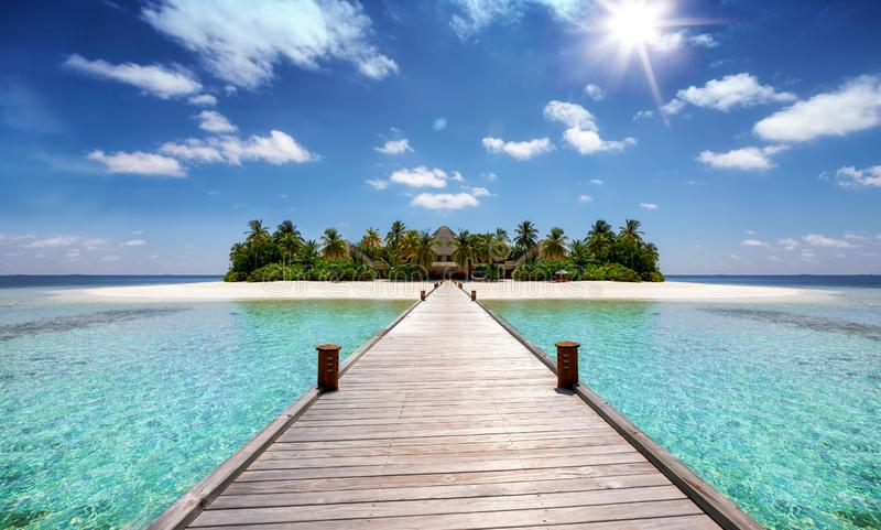 A wooden pier leading to a tropical paradise island stock photos