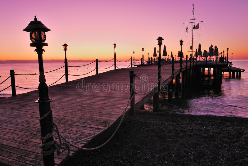 Wooden pier lighted by pink sunrise glow. Wooden pier lighted by sunrise glow stock photography