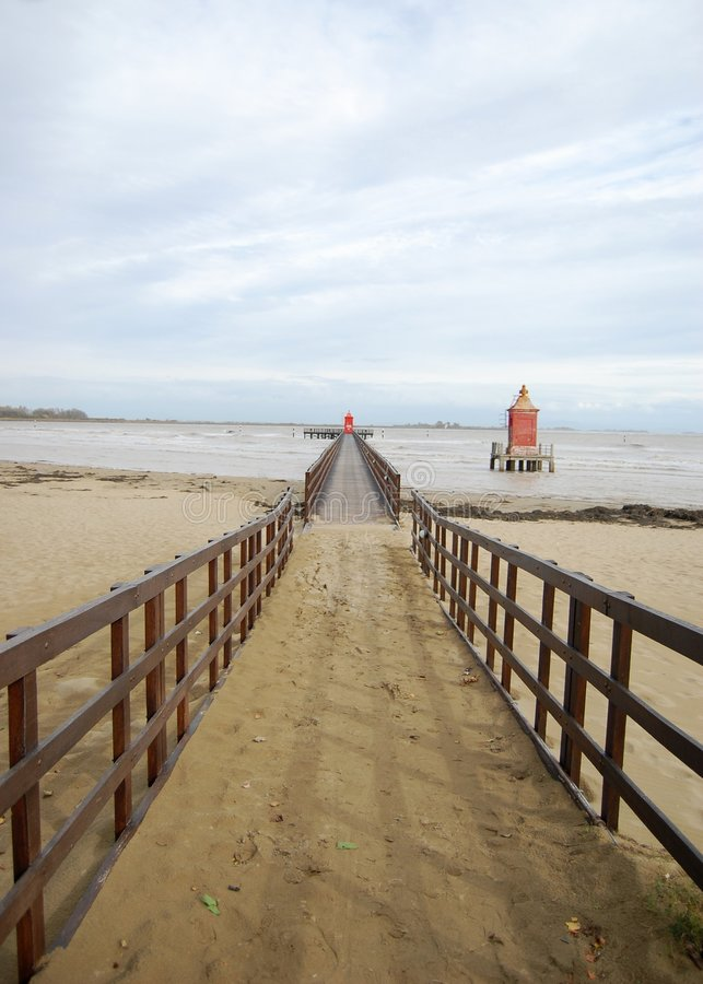 Wooden pier and lighthouse stock images