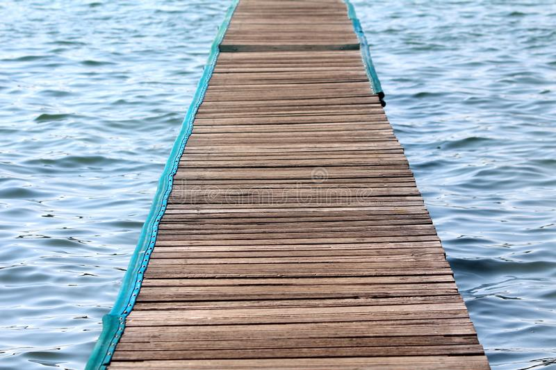 Wooden pier made of multiple narrow boards with nylon protection on edges over calm blue sea. On warm sunny day royalty free stock images