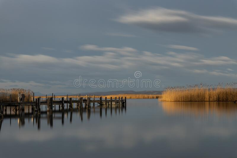 Wooden pier near the sea reflecting on it under the beautiful cloudy sky. A wooden pier near the sea reflecting on it under the beautiful cloudy sky stock image