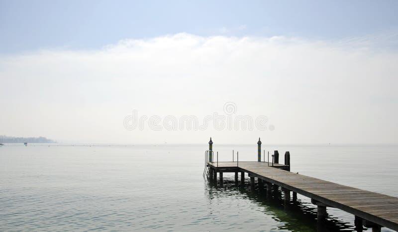 Wooden pier over lake against sky. Bardolino, Italy stock image