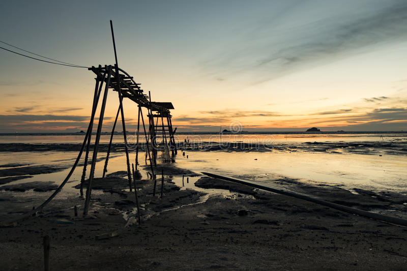 Wooden pier over magical light during sunset background.muddy beach and soft cloud royalty free stock photography