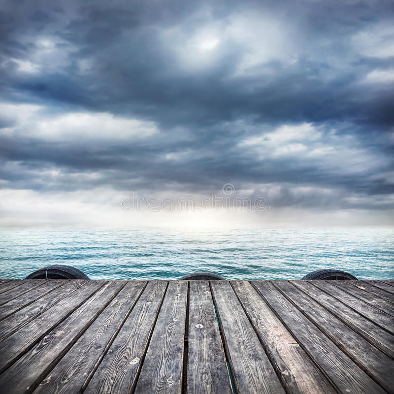 Wooden pier at overcast sky. Pier with wooden floor at dramatic overcast sky background royalty free stock photo