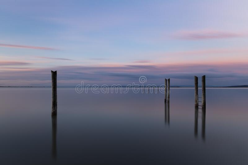 Wooden pier reflecting on the sea under the beautiful sunset sky. A wooden pier reflecting on the sea under the beautiful sunset sky royalty free stock photos
