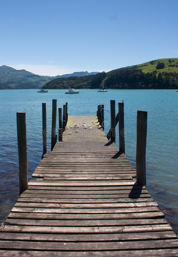 A wooden pier, sea and green hills in Akaroa near Christchurch in the South Island in New Zealand. A wooden pier, sea and green hills in Akaroa in the South stock images