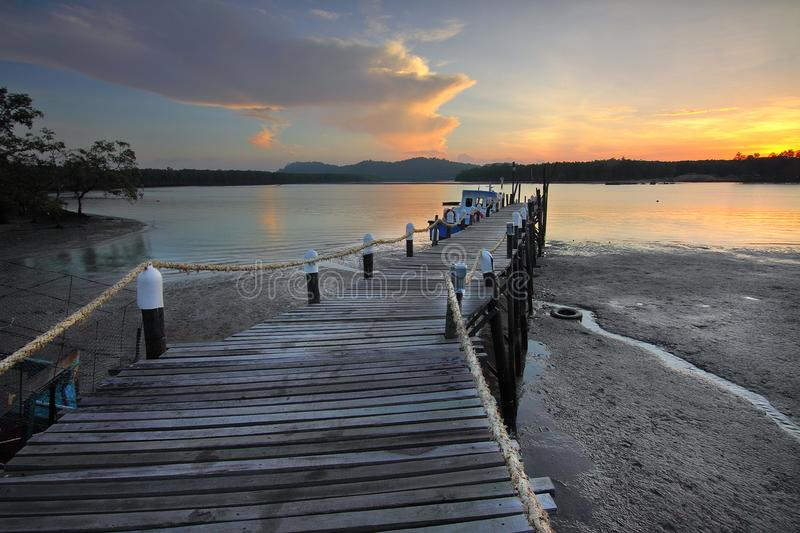 Wooden pier on seashore at sunset stock image