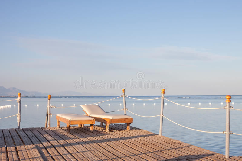 Wooden pier with sunbeds. Beautiful blue sky background stock photo