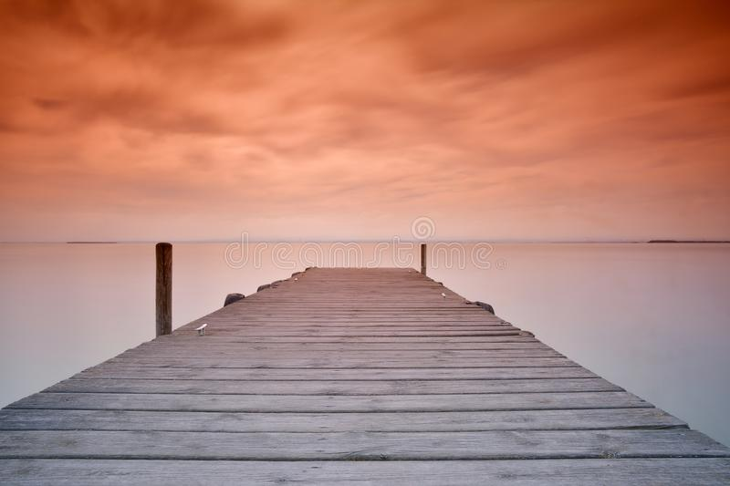 Wooden pier at sunset. View on scenic seascape with wooden pier at sunset of red and orange colors royalty free stock image