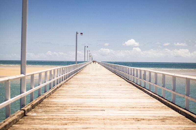Wooden pier in Urangan. A wooden pier with white metal railing and lampposts on a sandy beach in Urangan, Hervey Bay, Queensland, Australia royalty free stock photography